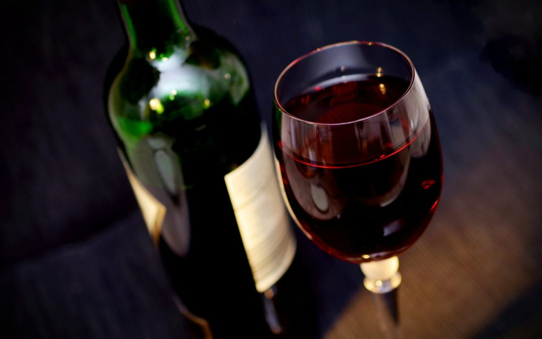 A bottle and a glass of red wine.